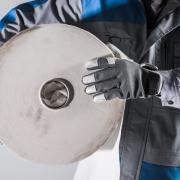 Arbeiter in der Papierindustrie hält Papierrolle